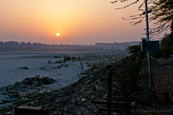 Sunset over barbed wire fence along Yamuna River