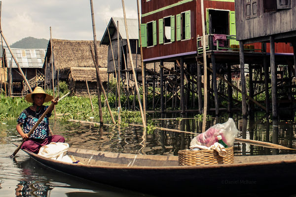 Local woman paddling boat on Inle Lake