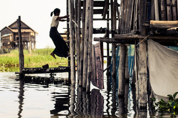 Burmese woman climbing into stilt house on Inle Lake