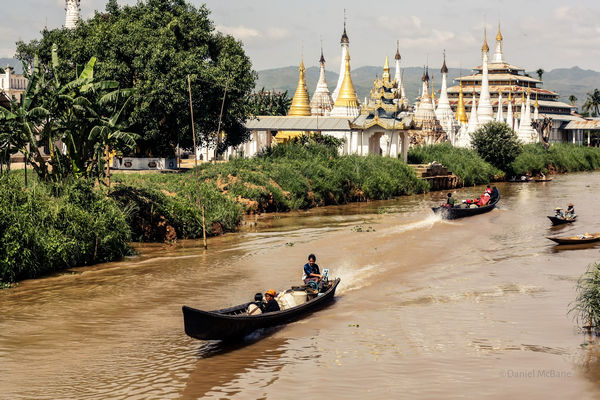 Boat passing temple and stupas on Inle Lake