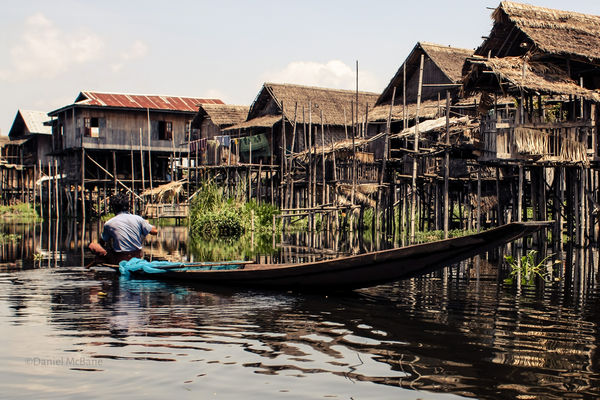 man in boat in stilt house village Myanmar