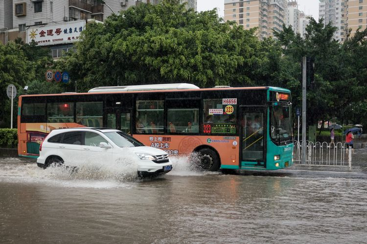 Car passes bus on flooded road in China