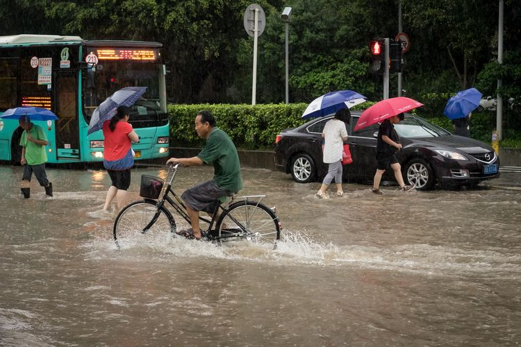 Man biking through flooded streets of Shenzhen China
