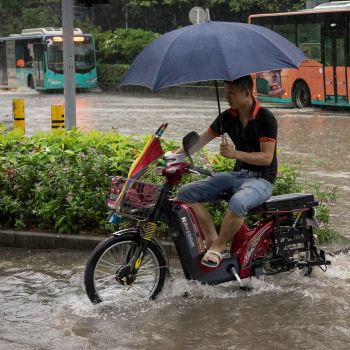 Man on electric bike in Shenzhen with umbrella