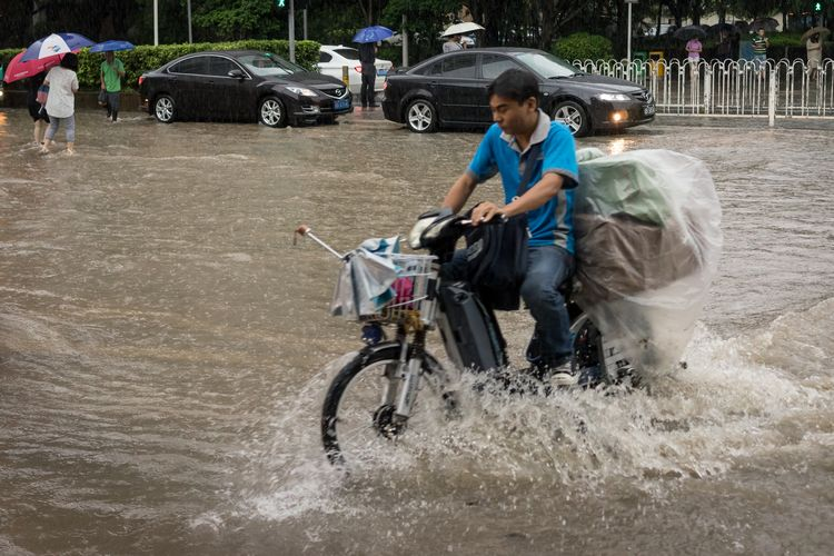 Man struggling through flooded Shenzhen street on motorbike