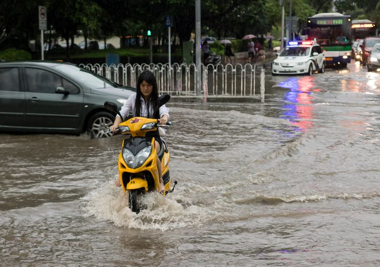 Chinese girl on motorbike in flood