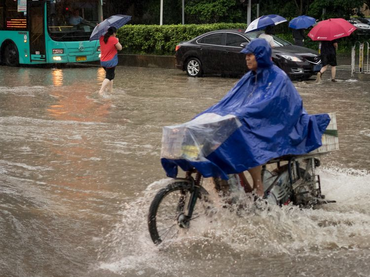 Man with poncho on motorcycle in Shenzhen flood